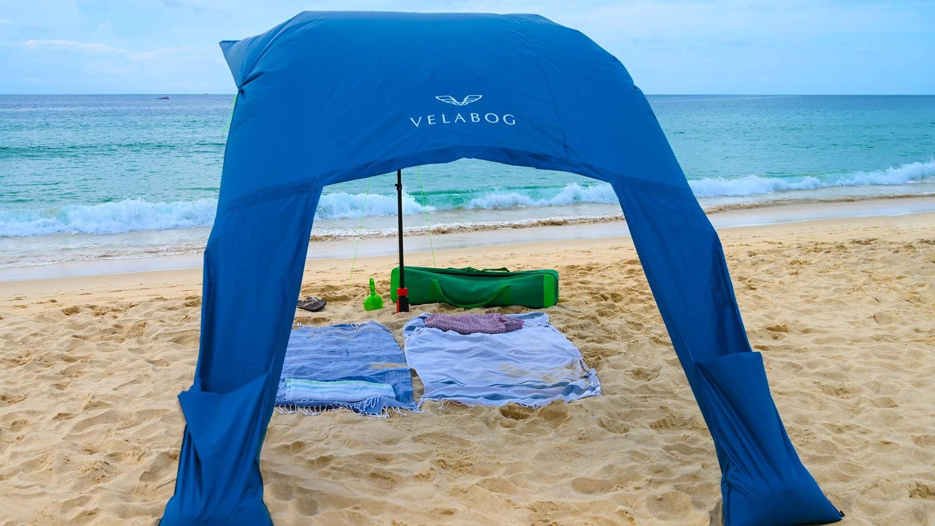 Velabog sun sail «Breeze» blue on the beach with a light breeze. Sun sail, beach umbrella and beach tent in one. High. Pleasant air circulation. View from behind.