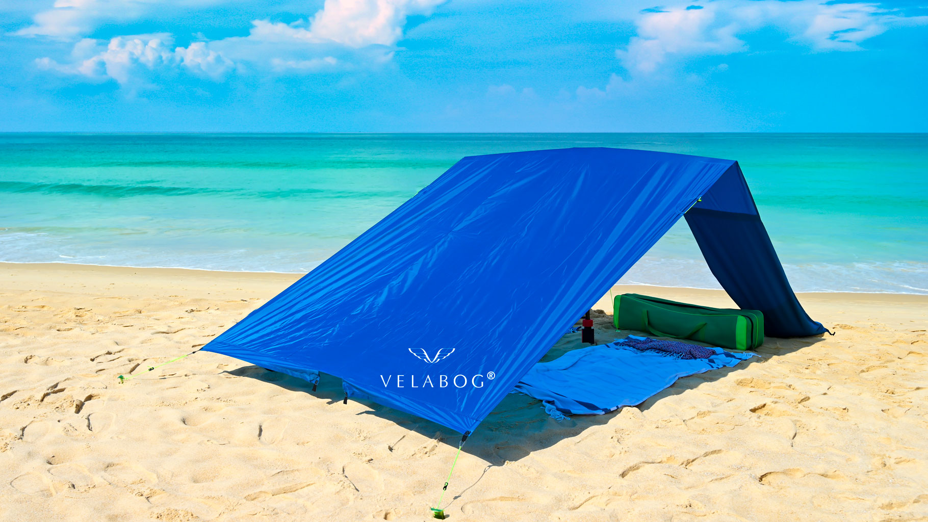 Velabog sun sail «Breeze» blue on the windless beach. Sun sail, beach umbrella and beach tent in one. Can also be used without wind. No heat build-up. Very large and stable. View from behind.
