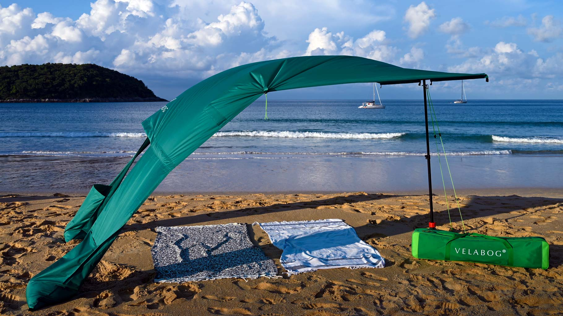 Velabog sun sail «Breeze» green on the windy beach in Thailand. Sun sail, beach umbrella and beach tent in one. High quality, stylish. Long service life. Side view.