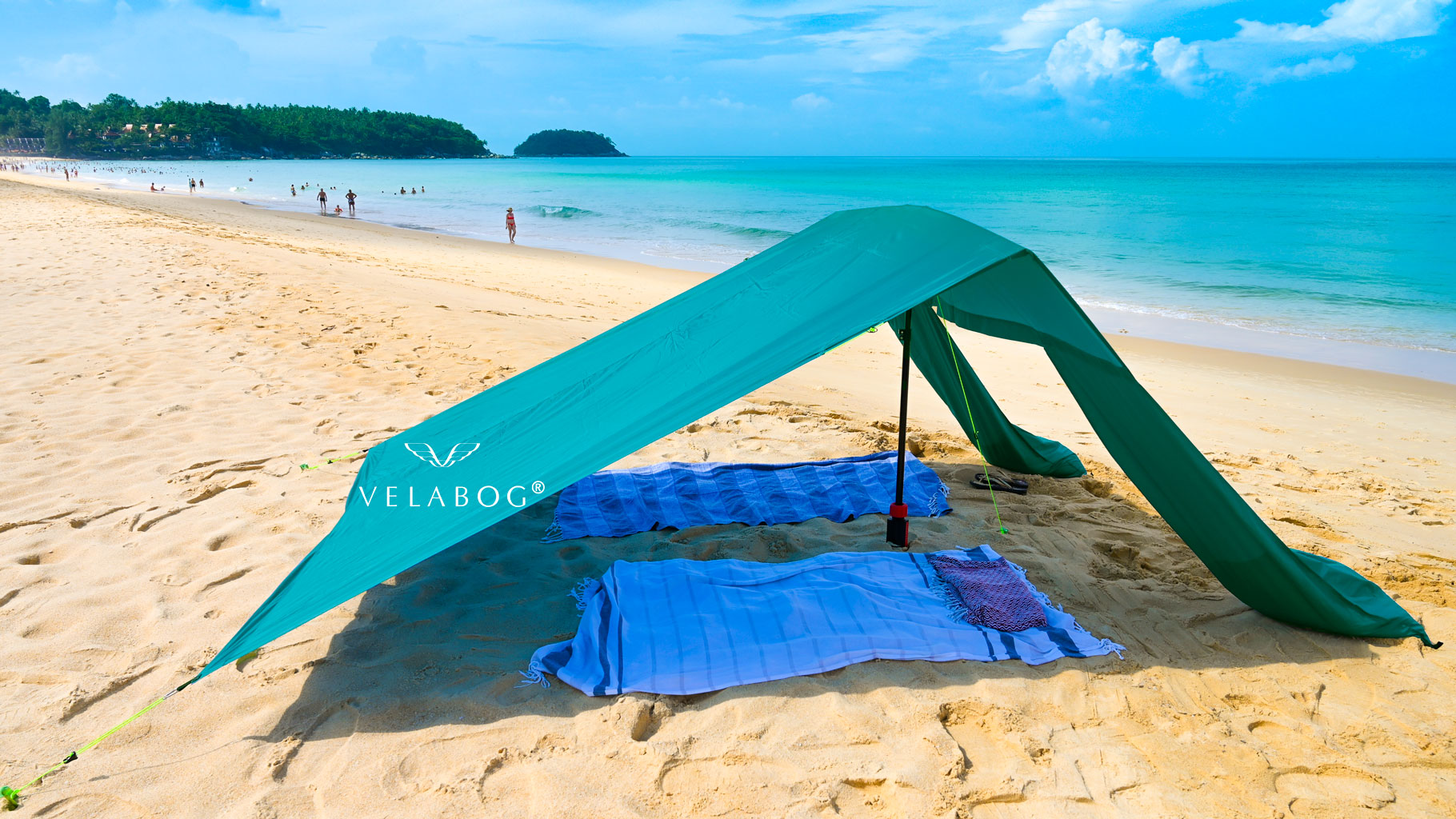Velabog sun sail «Breeze» green on the windless beach. Sun sail, beach umbrella and beach tent in one. Thanks to its light weight, it is easy to go far from the crowds. Flexible and independent.