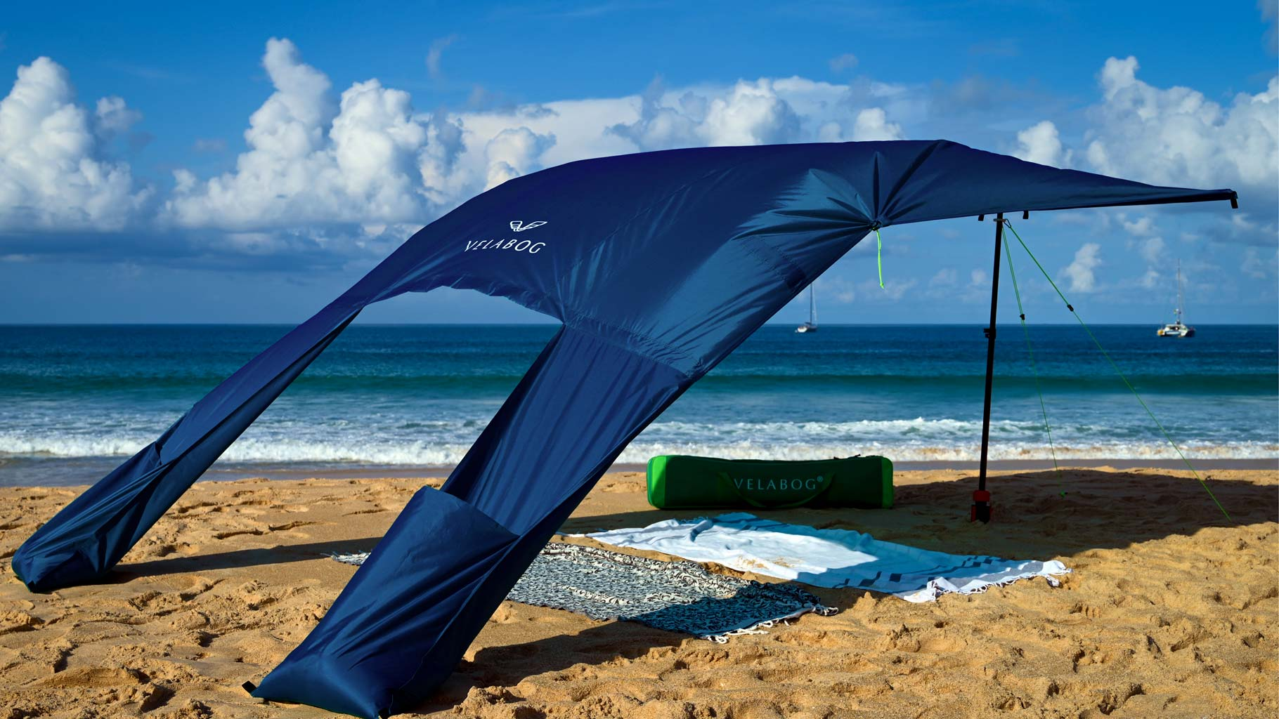 Velabog sun sail «Breeze» nightblue on the windy beach. Sun sail, beach umbrella and beach tent in one. Very large and yet compact. View from behind.