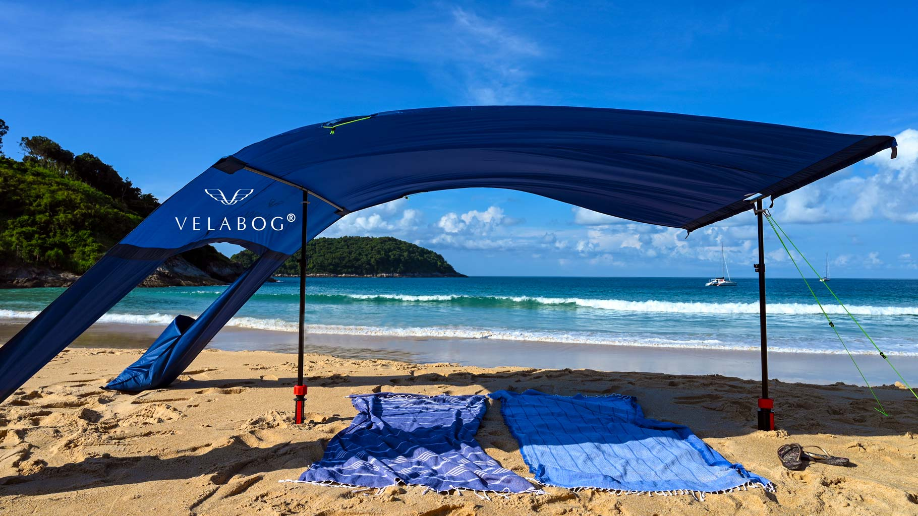 Velabog sun sail «Breeze» nightblue with extension set on the beach with gusty wind. Sun sail, beach umbrella and beach tent in one. Provides plenty of shadow in any type of wind, whether weak, strong or gusty. Bottom view.