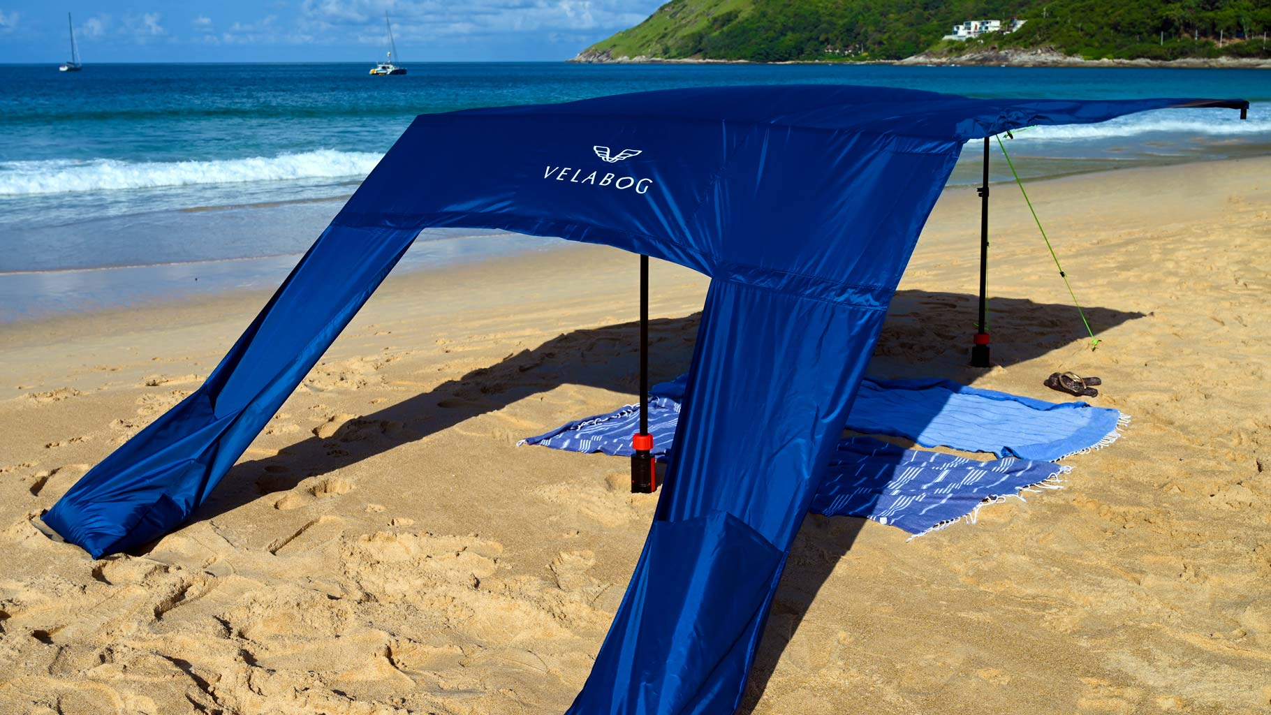 Velabog sun sail «Breeze» nightblue with extension set on the beach with gusty wind. Sun sail, beach umbrella and beach tent in one. Provides plenty of shadow in any type of wind, whether weak, strong or gusty. View from behind.